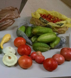 tomatoes, squash, cucumbers, yellow plastic bag with cherry tomatoes