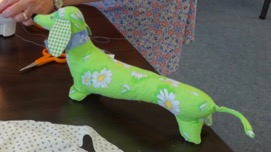 Stuffed animal, dachshund made out of green material with daisies on it.