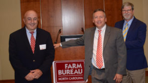Administrators from NC State University's College of Agriculture and Life Sciences stand by a podium while smiling. From left to right the faculty include Rich Bonanno, associate dean and director of NC State Extension; Richard Linton, dean of the College of Agriculture and Life Sciences; and Steve Lommel, associate dean and director of the North Carolina Agricultural Research Service.