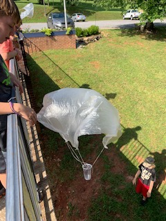 A child dropping a homemade parachute from a second story landing.