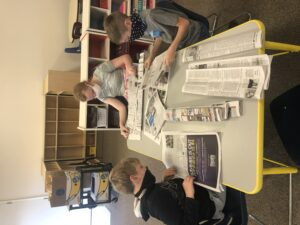 2 boys and a girl folding newspapers.