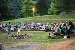 About 100 youth sitting on bleachers around a campfire watching a man talk