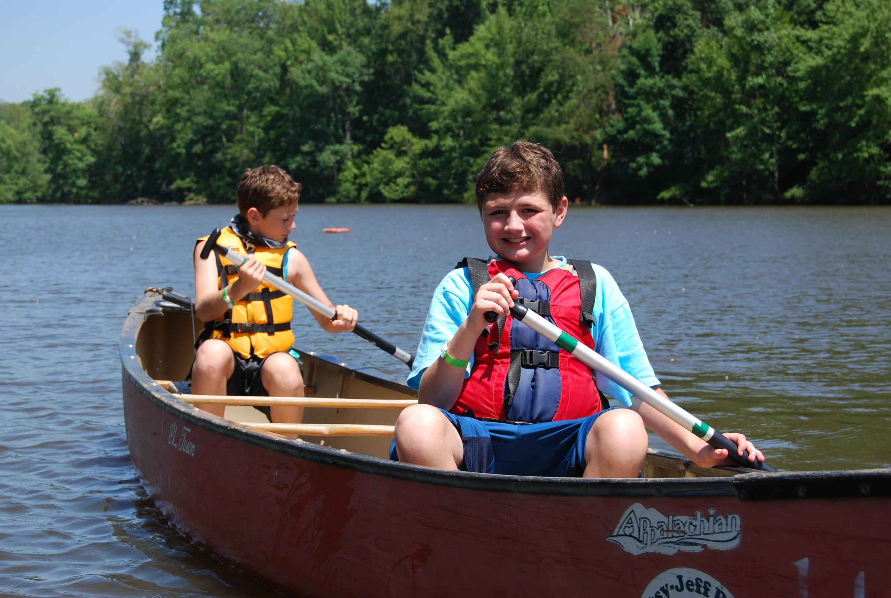 Two boys in a canoe on a lake paddling.